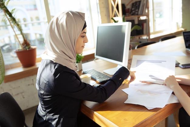 Talking on phone attented beautiful arabian businesswoman wearing hijab while working