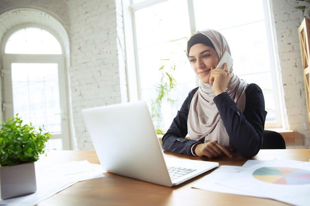 Talking on phone attented beautiful arabian businesswoman wearing hijab while working at
