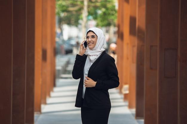 Parlando al telefono. bellissimo ritratto musulmano di donna d'affari di successo, ceo, leader, capo o manager felice e fiducioso. utilizzo di dispositivi, gadget, lavoro in movimento, sembra occupato. affascinante. inclusivo, diversità.