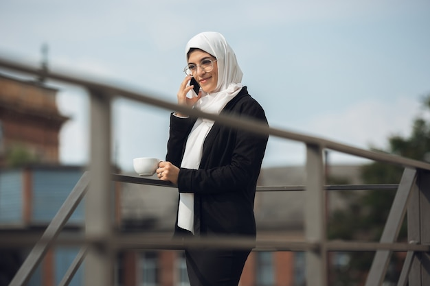 Talking on phone. beautiful muslim successful businesswoman portrait, confident happy ceo, leader, boss or manager. using devices, gadgets, working on go, looks busy. charming. inclusive, diversity.