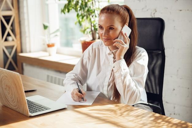 Talking on phone. caucasian young woman in business attire working in office. young businesswoman, manager doing tasks with smartphone, laptop, tablet has online conference. concept of finance, job.