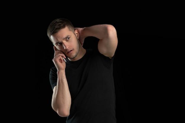 Parlando al telefono. ritratto monocromatico di giovane uomo caucasico isolato sulla parete nera. bellissimo modello maschile. emozioni umane, espressione facciale, vendite, concetto di annuncio. cultura giovanile.