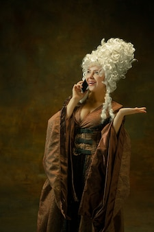 Talking on phone. portrait of medieval young woman in brown vintage clothing on dark background. female model as a duchess, royal person. concept of comparison of eras, modern, fashion, beauty.
