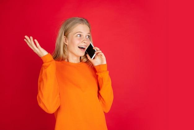 Говорящий телефон. портрет молодой кавказской женщины изолированной на красной предпосылке студии с copyspace. красивая женская модель. понятие человеческих эмоций, выражения лица, продаж, рекламы, молодежи. листовка