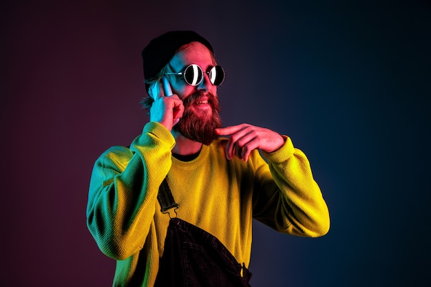 Talking on phone in sunglasses. caucasian man's portrait on gradient studio background in neon light. beautiful male model with hipster style. concept of human emotions, facial expression, sales, ad.