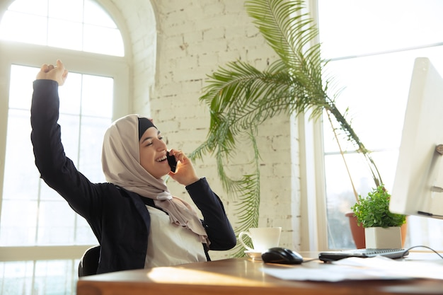 Talking on phone while drinking coffee. portrait of a beautiful arabian businesswoman wearing hijab while working at openspace or office. concept of occupation, leadership, success, modern solution.