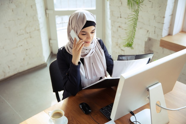 Talking on phone while reviewing docs. beautiful arabian businesswoman wearing hijab while working at openspace or office. concept of occupation, freedom in business area, success, modern solution.