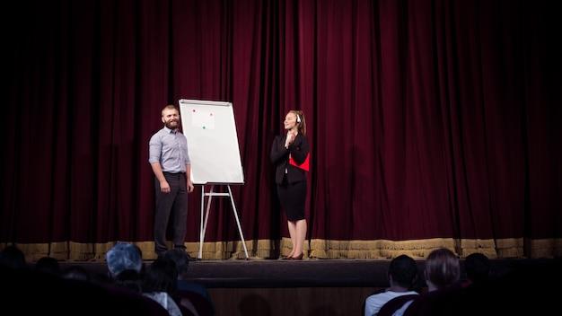 Parlare con gli studenti. altoparlante femminile che dà la presentazione nella hall al workshop. centro affari. vista posteriore dei partecipanti al pubblico. evento congressuale, formazione.