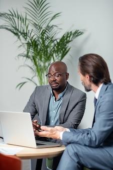 상사와 이야기. 노트북 근처에 앉아서 상사와 이야기하는 검은 피부의 열심히 일하는 직원