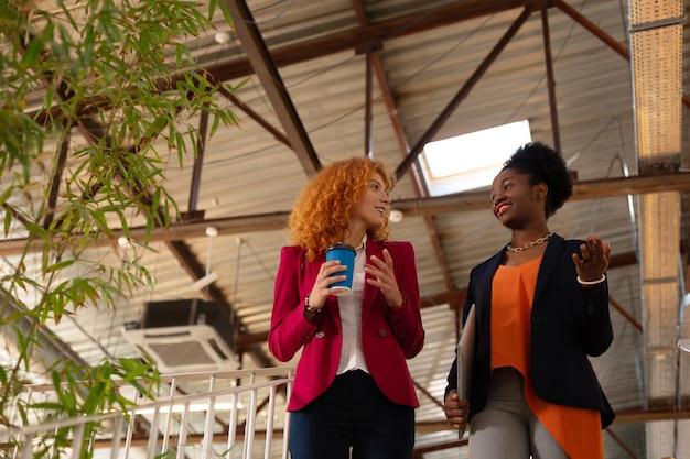 同僚と話しています。コーヒーを飲み、同僚と話している巻き毛の赤毛の労働者