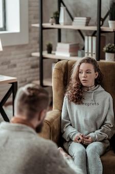 카운슬러와 대화. 카운슬러와 이야기하는 동안 안락 의자에 앉아 매력적인 세련된 십대 소녀