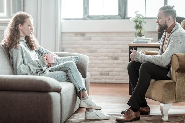 카운슬러와 대화. 그녀의 개인 상담원과 이야기하는 청바지와 회색 까마귀를 입고 아름다운 곱슬 소녀