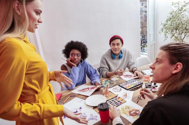 従業員と話す。彼女の従業員と話している黄色のドレスを着ているブロンドの髪の魅力的なマネージャー