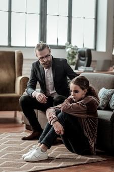 父に話しかける。床に座って意気消沈した娘に話している思いやりのあるひげを生やした父親