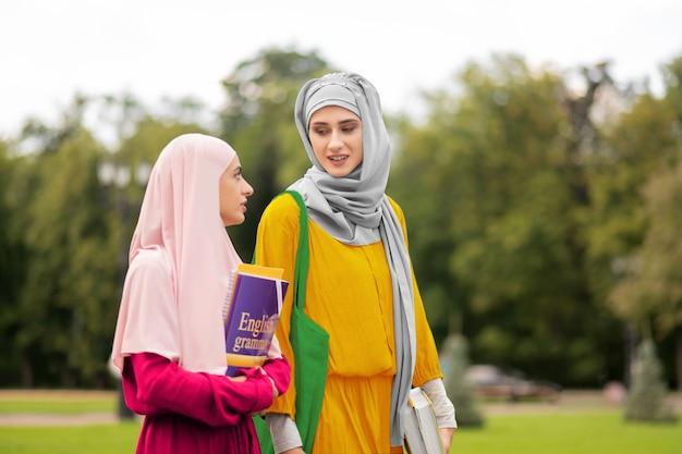 친구와 이야기. 함께 걷는 동안 친구에게 이야기하는 노란색 드레스를 입고 이슬람 학생