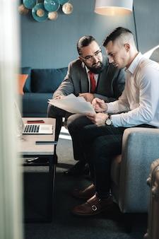彼の若い助手と話しています。肘掛け椅子に座っている彼の若いアシスタントと話しているひげを生やした黒髪のビジネスマン