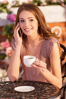 Talking with friend. attractive young woman talking on the mobile phone and smiling while sitting at the outdoor cafe