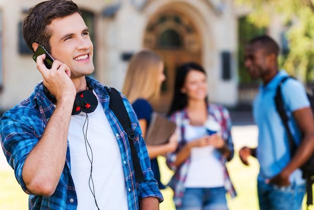友達と話している。携帯電話で話し、バックグラウンドでチャットしている彼の友人と大学の建物に立って笑っているハンサムな若い男