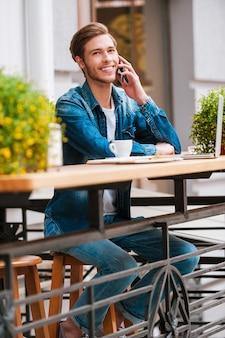 友達と話している。携帯電話で話し、笑顔で幸せな若い男