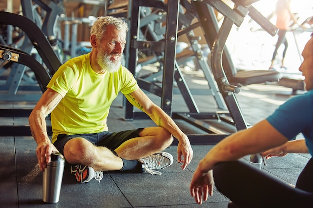 Talking with personal trainer happy middle aged man discussing something with fitness instructor