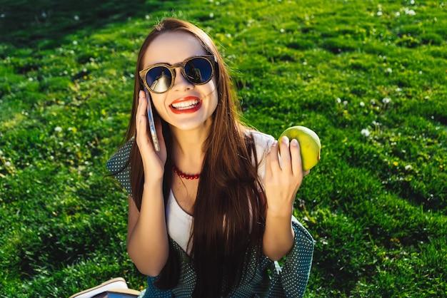 말하는 여자는 휴대전화를 들고 드레스, 선글라스를 끼고 잔디에 앉아 있다