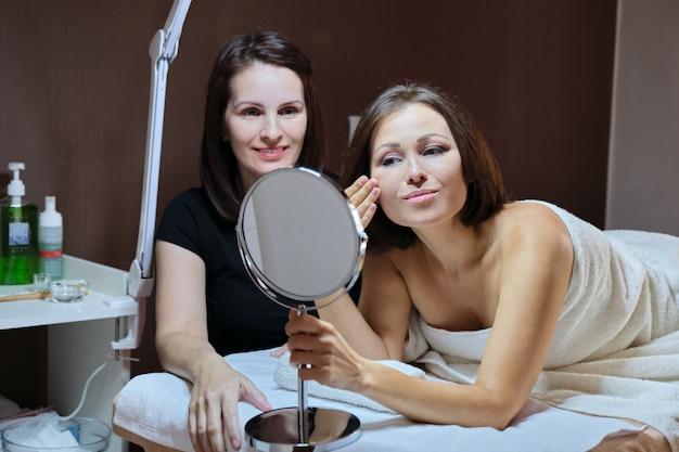 Говорящая женщина косметолог и зрелая женщина с зеркалом в салоне красоты
