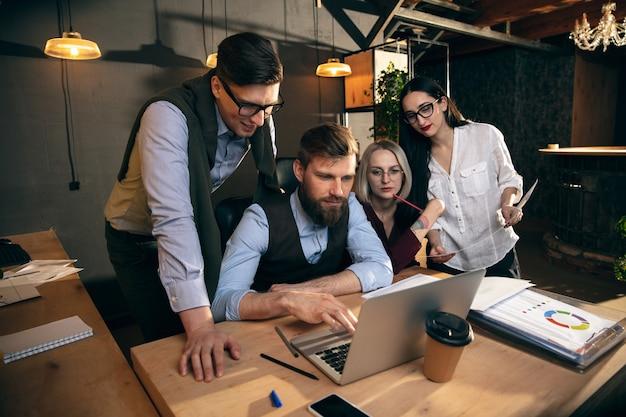 Беседы. коллеги работают вместе в современном офисе с помощью устройств и гаджетов во время творческой встречи.