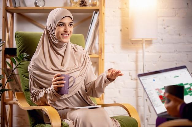 コーチと話します。オンラインレッスン中に自宅で幸せなイスラム教徒の女性。現代のテクノロジー、遠隔教育、民族性、伝統の概念。人間の感情、ライフスタイル。自宅に座っているラップトップを使用します。