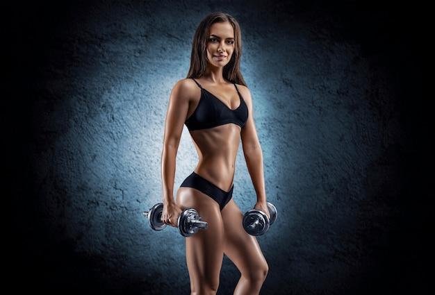 Высокая взрослая женщина с красивыми волосами позирует в спортивной одежде. концепция фитнеса и бодибилдинга. смешанная техника