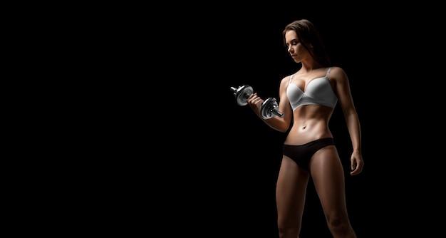 Высокая взрослая женщина с красивыми волосами, позирует с гантелями в руке. концепция фитнеса и бодибилдинга. смешанная техника