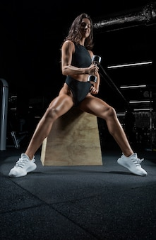 Tall athletic woman posing in the gym on a bench with dumbbells. biceps pumping.