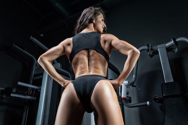Высокая спортивная женщина позирует в тренажерном зале. вид сзади.