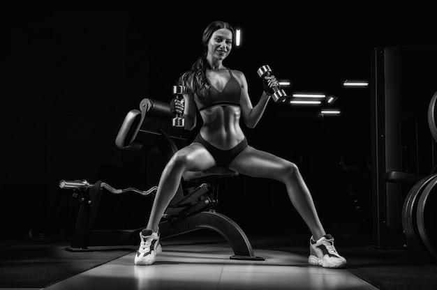 Высокая спортивная женщина позирует в тренажерном зале на скамейке с гантелями.