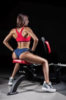 Высокая спортивная женщина позирует в тренажерном зале на скамейке. вид сзади.