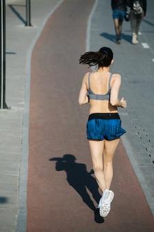 야외 산책로 옆에 있는 새 트랙에서 키가 큰 운동선수가 도망치고 있습니다. 맑고 푸른 하늘 아래 화창한 날. 그녀는 회색 상의와 미니 반바지를 입고 있습니다.