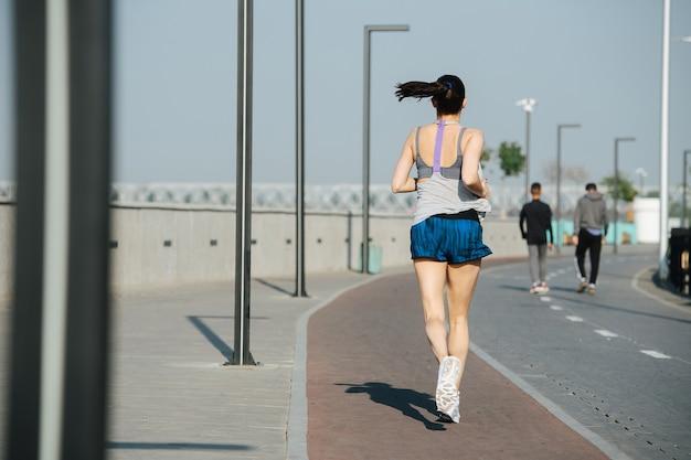 야외 산책로 옆에 있는 새 트랙에서 키가 큰 운동선수가 도망치고 있습니다. 맑고 푸른 하늘 아래 화창한 날. 그녀는 흰색 민소매 셔츠와 미니 반바지를 입고 있습니다.