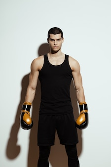 Tall attractive sportsman posing in boxing gloves