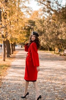 暖かい赤いコート秋の流行のファッション、ストリートスタイル、ベレー帽の帽子をかぶって公園を歩いている巻き毛の背の高い魅力的なスタイリッシュな笑顔の細い女性