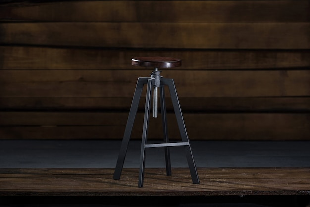Tall bar stool on a wooden background