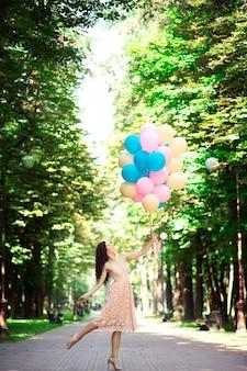드레스와 곱슬 머리에 키 크고 아름다운 날씬한 소녀는 여름에 공원에서 여러 가지 빛깔의 풍선을 들고있다