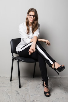 Tall brunette girl in glasses dressed up in white t-shirt and black pants sits on office chair in front of white background