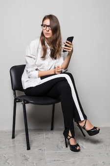 Tall brunette girl in glasses dressed up in white t-shirt and black pants sits with phone on office chair in front of white background