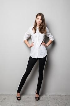 Alta ragazza bruna con gli occhiali vestita in maglietta bianca e pantaloni neri si trova davanti a sfondo bianco