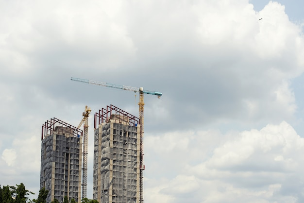 Tall building under construction and have a crane in the construction site