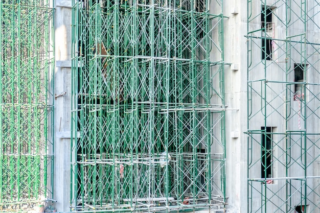 Tall building under construction with green scaffolds.