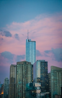 Tall business building skyscraper in chicago, us, with beautiful pink clouds in the blue sky