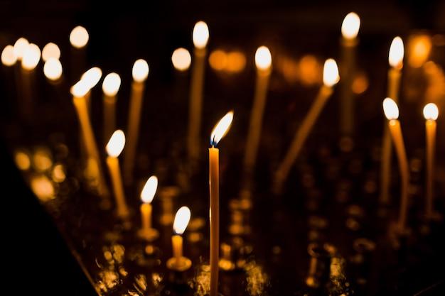 Высокие свечи сияют на стальной тарелке
