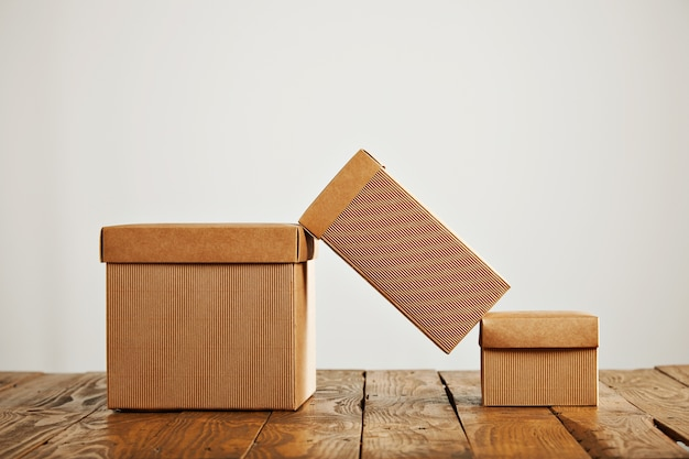 A tall cardboard box balanced on top of two similar boxes with covers in a studio setting isolated on white