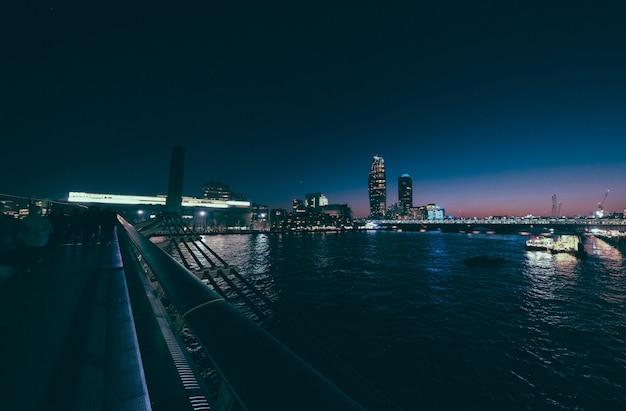 Edificio alto e città in lontananza sparato dal millennium bridge di notte