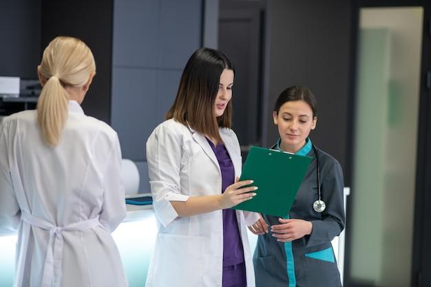 Высокий темноволосый доктор держит в руках лист задания